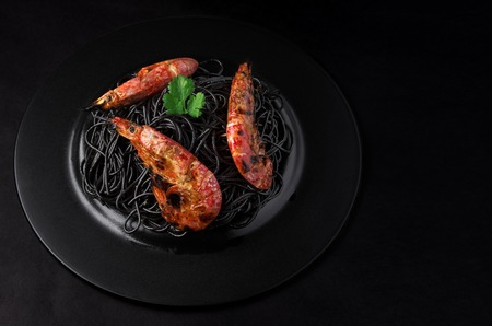 marinara sauce: Black spaghetti with shrimps on a black plate and black background with copy space.