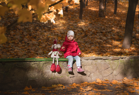 He is sitting thoughtful little girl in a red jacket, next to a plush mouse, in a park outdoors in the fall, around the beautiful foliage