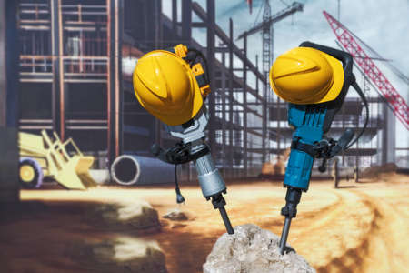 Two electric jackhammers and a helmet, stick out of a concrete block, against the background of a construction poster.