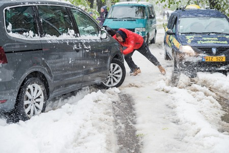Chisinau, Republic of Moldova - April 20, 2017: Genre weather, snow. Abnormal cold spell in April . People are pushing out of a snowdrift a car stuck in the snow. The Snow Cyclone. Editorial