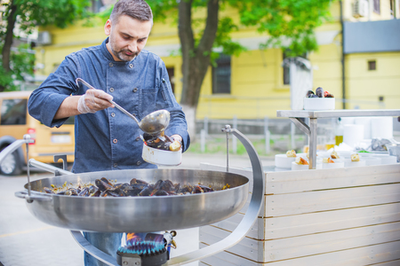 The chef prepares mussels in a large frying pan on the street, street food Stock Photo