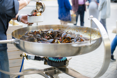 The chef puts mussels, seafood salad. Lovely lunch or dinner. Live healthy food. Close-up of a diver in his hand and a plate of mussels. Stock Photo