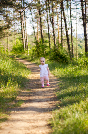 Little girl wearing pink dress taking a walk all alone in a park or forest, eating an apple slice.