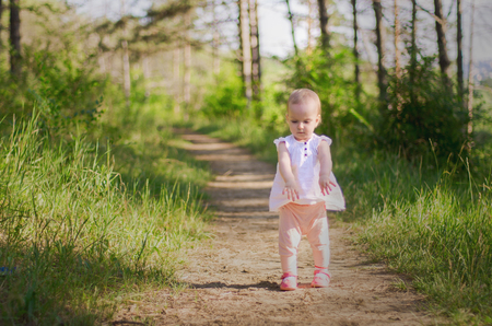 Little girl wearing pink dress taking a walk all alone in a park or forest, view from the back.