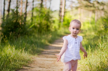 Little girl in pink trousers, walking alone in a park or forest, gives her hands to the side
