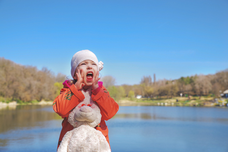 Closeup portrait of a screaming girl, in the park on the background of the lake