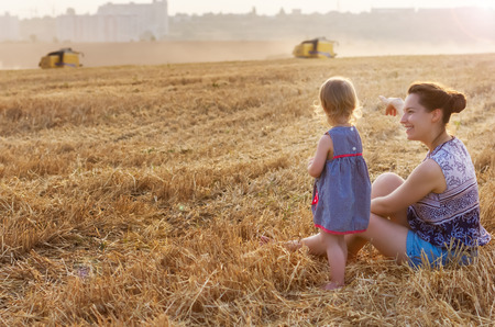 Happy family: a young beautiful woman with her little cute daughter, sit in the orange field on a sunny summer day. Parents and kids relationship. Nature in the country.