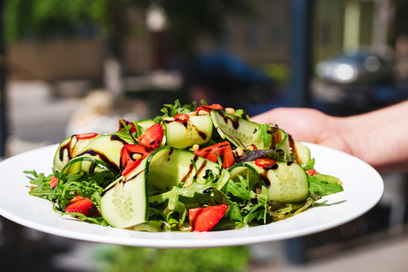 Summer salad with arugula, strawberries and cucumber, a plate in hand on a terrace background.