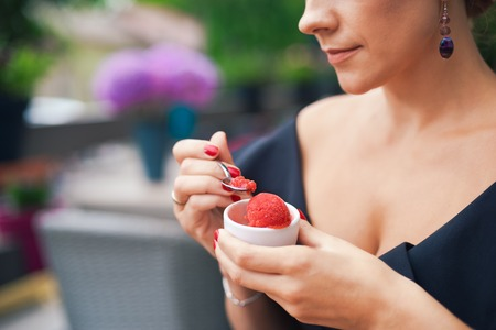 womans hand: Closeup of a womans hand holding a cup with homemade red ice cream. Breakfast, snacks. The concept of healthy eating and lifestyle. Stock Photo