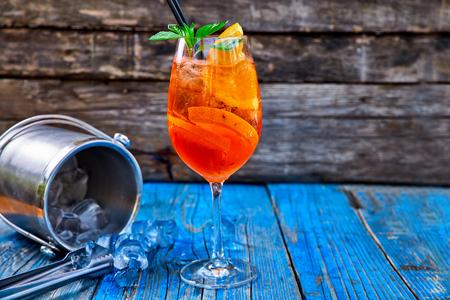 Spritz Aperol-cocktail in een glas en ijsblokjes op een rustieke houten achtergrond, exemplaarruimte. Stockfoto