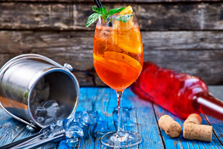 Spritz Aperol cocktail in a glass and ice cubes on a rustic wooden background, copy space. 版權商用圖片