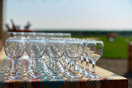 beautiful holiday table glasses of wine glassestwo rows of glasses on a table with a white tableclothglasses on high legsplaced a glass of wine on festive table. Close up. Outdoor catering.