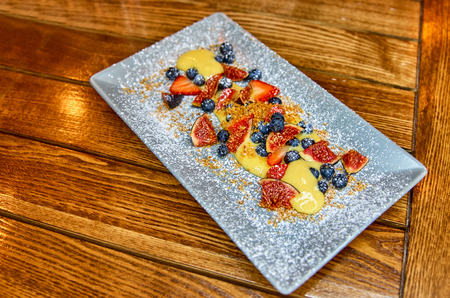 Italian dessert. Cream Sabayon with forest, winter berries. Light dessert with white wine on a plate. Wooden background.