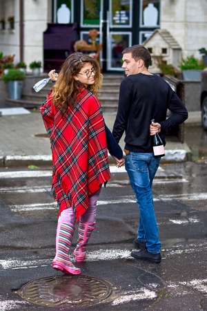 Young woman with long hair wearing glasses, wearing rubber boots, Young guy with champagne in hand, smiling happily, embracing crossing the street. Concept of alcoholism. Close-up.