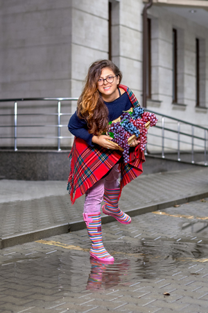 Young woman - teenage girl with long hair in glasses, with a basket of grapes, smiling happily, in rubber boots standing in a puddle on the street.