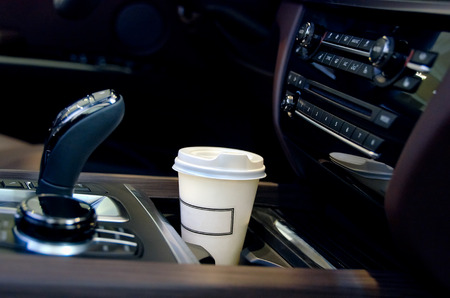 Coffee in the car salon. A single paper coffee cup inside the car cup holder.