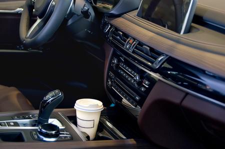 車のサロンでコーヒー。車のカップホルダーの中に1枚の紙のコーヒーカップ。