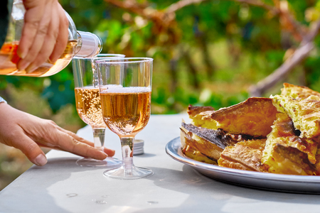 Female hands pour refreshing pink wine in a glass with cakes on the table, against the background of the vineyard. Sunny day, the concept of winemaking.