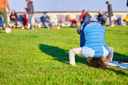 petite fille debout sur la tête sur l'herbe dans le parc. Concept d'enfance, prêt pour votre texte, logo ou symboles. Banque d'images