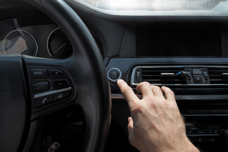 Pictures of the beginning of the journey by car,Focus on finger. hand presses the start button of the car