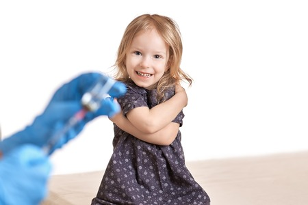 healthcare and medical concept - Little happy girl before getting an injection, vaccine, on white background.