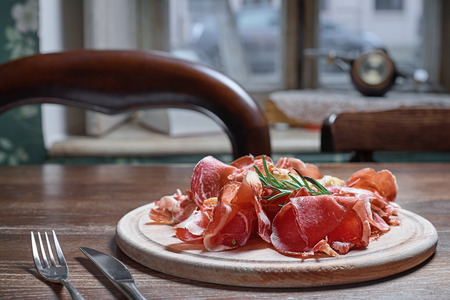Wooden cutting board with prosciutto cheese on wooden table background. Close-up
