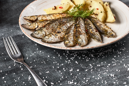 Traditional Spanish barbecue sardines with boiled potatoes, on a plate close up. horizontal , selective focus. Concept of healthy food. Stockfoto