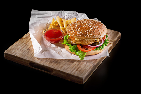 burger with french fries on wooden cutting board isolated on black background, close-up shot, selective focus. Banque d'images - 97968857