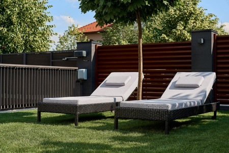 Two chaise lounges are on the green lawn in the courtyard of the house. Concept of relaxation, rest, weekend. Stock Photo