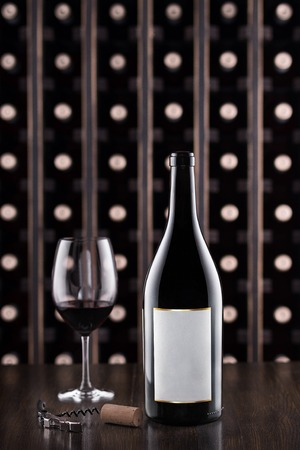 Glass of wine and wine bottle. Wine testing at the storage. Wine cellar.with space for text, selective focus