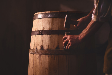 the master makes a wooden barrel for brandy, oak boards compresses them with iron rings Imagens