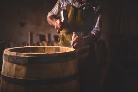 the master makes a wooden barrel for brandy, oak boards compresses them with iron rings Stok Fotoğraf