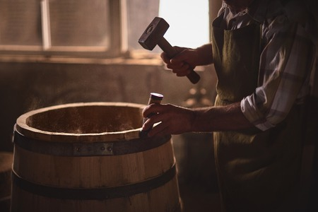 the master makes a wooden barrel for brandy, oak boards compresses them with iron rings Stock Photo