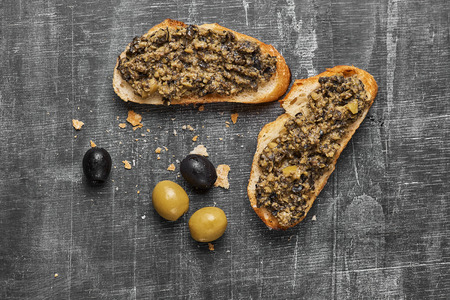 Bruschetta with green olives, anchovies,capers, selective focus, top view close-up 免版税图像
