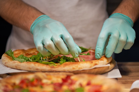 Chef making a parma or prosciutto ham Italian pizza in a close up view of his hands placing the meat