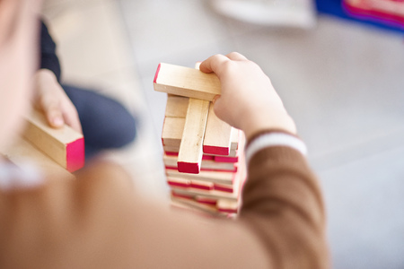 The child plays in a tower of wooden bars. Floors of wooden pieces. The child takes out the bars from the floors of the tower. Board game. Learning and education concept. Top view