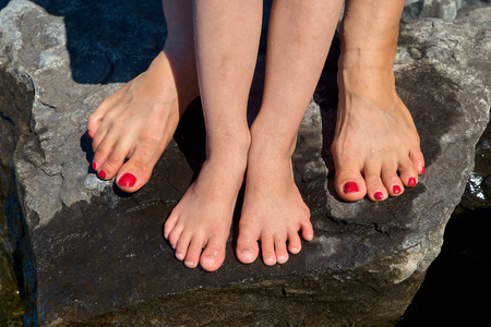 Two pairs of childrens and womens feet with a manicure, wet feet on the stone, a beach, a warm hot resort. Close-up