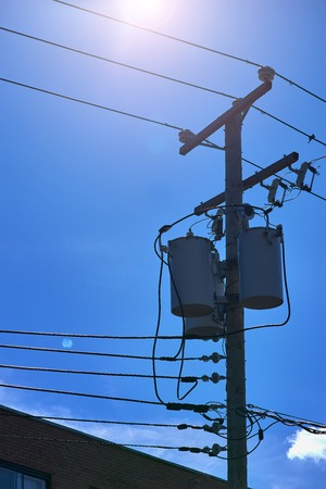Energy and technology: electrical post by the road with power line cables, transformers against bright blue sky providing copy space. 스톡 콘텐츠