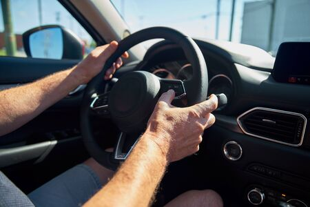 Man driving a car with two hands on the steering wheel. On a hot day, the concept of the right driving, safe.
