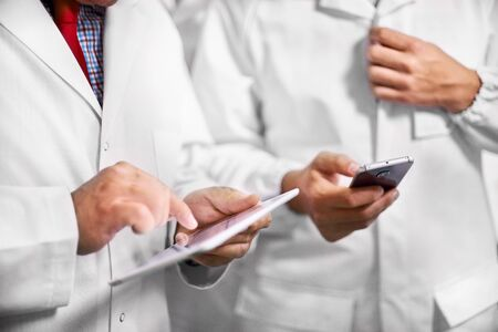 Employees confer stand in white coats using a tablet computer and telephone. close up of hand with computer tablet, selective focus