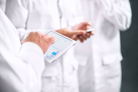 Employees confer stand in white coats using a tablet computer and telephone. close up of hand with computer tablet, selective focus Banco de Imagens