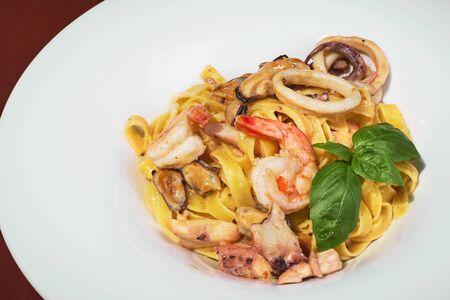 Pasta with shrimps, calamari, fresh parmesan cheese on a wooden table, terrace, seafood, fish dish. Fresh food. Close up.