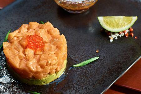 Fresh tartar with salmon dip in sauce, avocado, red caviar, on black plate. Fish dish. Fresh food. Clost up