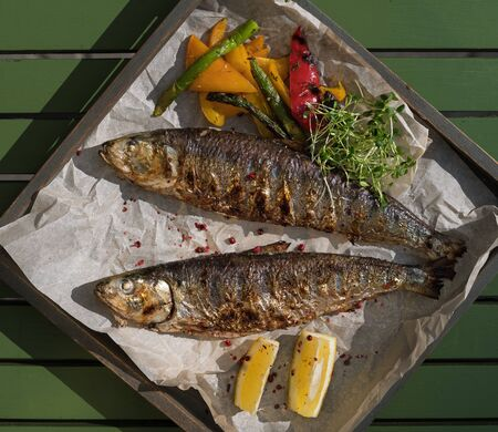 Grilled mackerel fish with baked vegetables on a wooden tray in the street, terrace, outdoor cafe, sunset. Free space for text.1:1