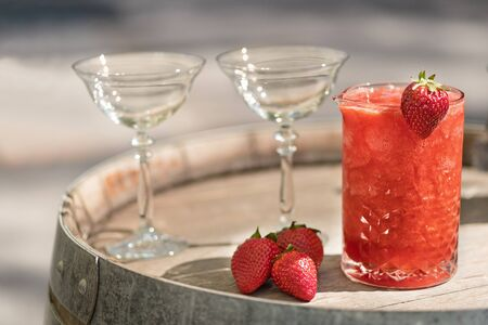 Summer Slushy made from strawberries, smoothies, ice with some ingredients nearby over wooden background. Daylight.