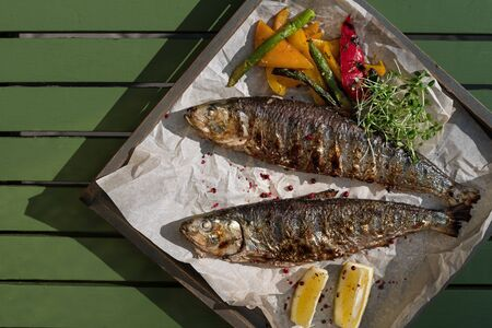 Grilled mackerel fish with baked vegetables on a wooden tray in the street, terrace, outdoor cafe, sunset. Free space for text.