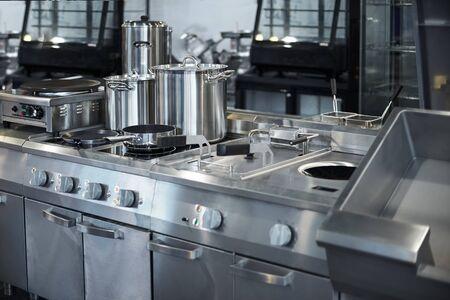 Encimera y menaje de cocina en cocina profesional, vista mesada en acero inoxidable. Bokeh.