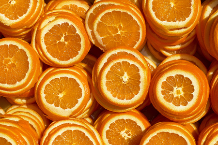 Background of ripe juicy orange slices. The texture of orange. Bright sunlight illuminates. Stock Photo