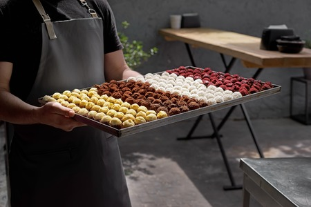 handmade chocolates, white, dark and milk chocolate and various types of cheese on a tray. Dessert Gourmet, on the terrace in the hand of the waiter. Imagens