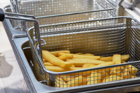 French fries cooking. Closeup view of making french fries deep frying in an equipment in fast food. The concept of fast food, delicious food, restaurant.